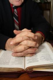 Händer knäppta i bön